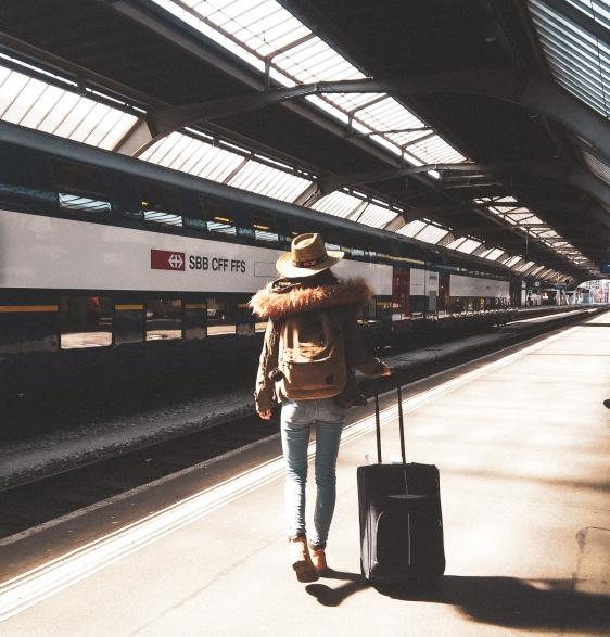 Chica de espaldas con maleta en el interraíl.