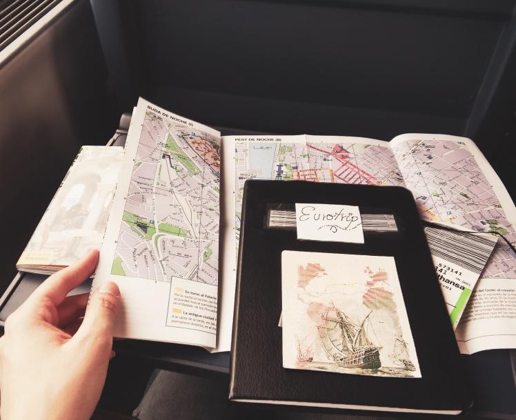 Fotografía de un cuaderno de viaje y mapas interraíl.